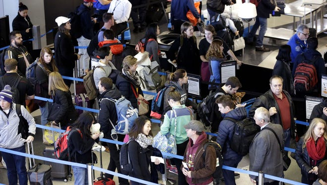 In this Sunday, Nov. 29, 2015, file photo, travelers line up at a security checkpoint area in Terminal 3 at O'Hare International Airport in Chicago.  The auto club AAA said Tuesday, Nov. 15, 2016, that it expects 1 million more Americans to venture at least 50 miles from home, a 1.9 percent increase over last year.