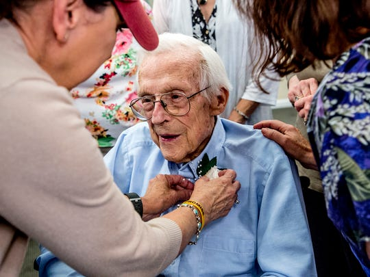 Donna Hamilton pins a flower onto Carl Nutter's shirt before the celebration for his 100th birthday began.