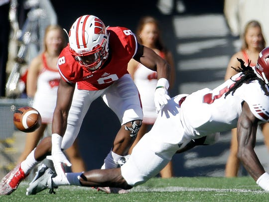 Wisconsin's Sojourn Shelton (8) breaks up a pass intended for Troy's Jarvis Bentley (3) during the first half of an NCAA college football game Saturday, in Madison.