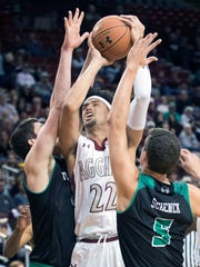 New Mexico State's Eli Chua goes up against Utah Valley's Andrew Bastien and Hayden Schenck during second half action Thursday night at the Pan American Center.