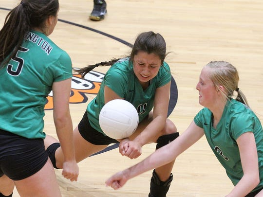 Farmington's Donna Hall, left, Jaydn Curry, center, and Alyssa Simmons try to keep the ball alive against Aztec on Saturday at Lillywhite Gym.