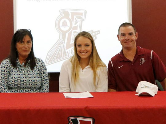 Loren Sayers is accompanied by her parents, Chris and Monika Sayers, at Wednesday's signing ceremony at Elmira High School.