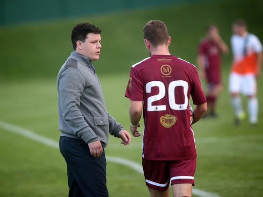 Detroit City FC manager Ben Pirmann talks to player Matt Nance during a match against the Michigan Bucks on May 11, 2016, at Oakland University.