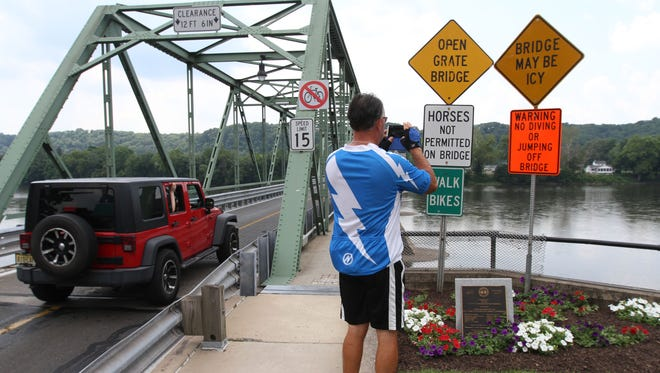 A man pauses to to take a picture of the Delaware River during the annual Bastille Day in Frenchtown on July 12, 2014.