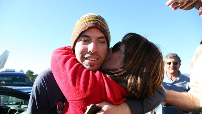Elsa McCarthy kisses her son, Christopher McCarthy, after he and three other mountain bikers were found safe by  search and rescue teams, after spending a night in the chilly Angeles National Forest near Pasadena, Calif., on Dec. 23, 2013.