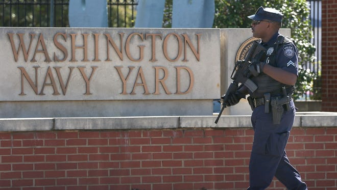 A police officer stands guard at Washington Naval Yard on Sept. 17, 2013, the day after a defense contractor named Aaron Alexis went on a shooting rampage.