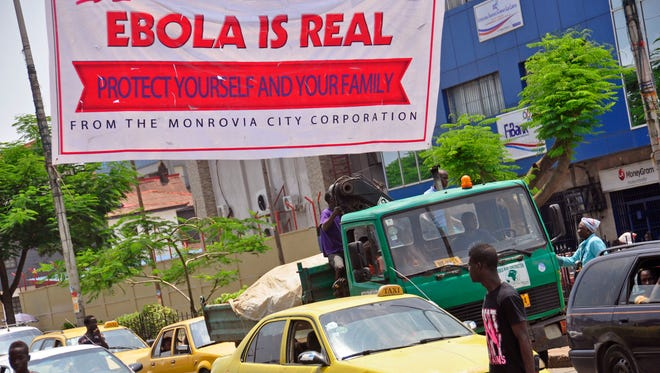 """A banner reading, """"Ebola is real. Protect yourself and your family"""" warns people of the Ebola virus in Monrovia, Liberia, on Aug. 2. The Ebola outbreak in West Africa has killed more than 880 people."""
