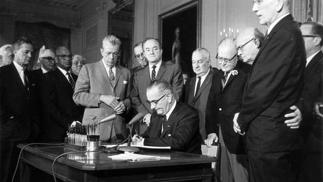 President Lyndon Johnson signs the Civil Rights Act of 1964.