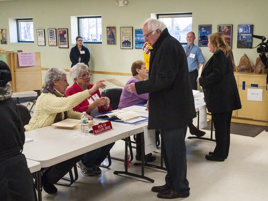 Democratic presidential candidate Sen. Bernie Sanders, I-Vt., receives his ballot before voting in Vermont's presidential primary in Burlington on Tuesday, March 1, 2016.