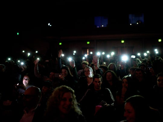 The crowd waves their smart phones as Mr. August Thomas