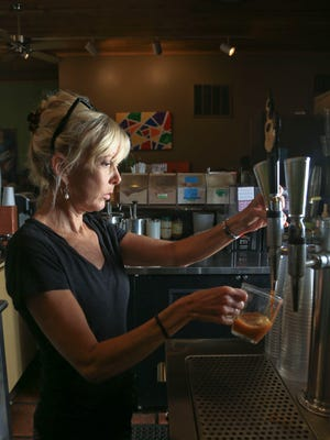 Natalie Hofer, co-owner of Highland Coffee, pours a nitro draft of coffee at the Highlands shop. The coffee is brewed hot, then stored in 5-gallon kegs and comes out of the tap cold. The coffee has an initial creaminess in taste, with a velvety feel in the mouth. It's a popular drink during the warmer months and Highland Coffee has offered the draft-style coffee for about three years.