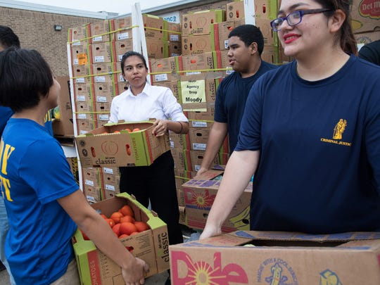 Moody High School students wait to load food packages into cars during the Trojan Mobile Food Pantry on Thursday, March 1, 2018.