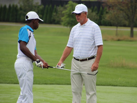 Bryce Henderson (left) listens to advice from golf