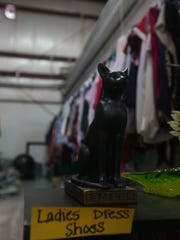 A tiny cat figurine sits in front of a clothing rack