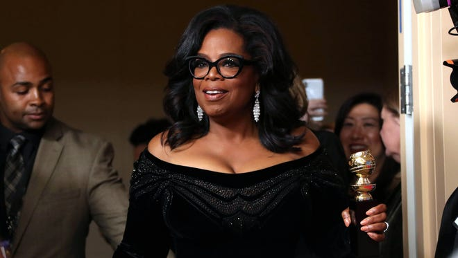 Oprah poses with her Golden Globe Cecil B. DeMille Award in the media room during the ceremony at the Beverly Hilton Hotel in Beverly Hills, Calif., on Sunday night.