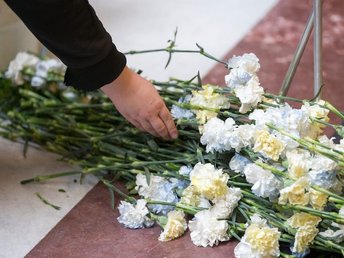 Attendees place flowers on the ground in a ceremony designed to honor Hoosiers who have died on the job during a Workers' Memorial Day, at the Indiana Statehouse, Indianapolis, Monday, April 28, 2014.