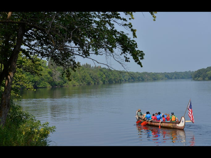 Kory Klebe of the Prairie Woods Environmental Learning Center in Spicer directs a group as they paddle a large, voyageurs canoe upstream Saturday during the Take a Day OFF on the Mississippi event at Mississippi River County Park near Rice.
