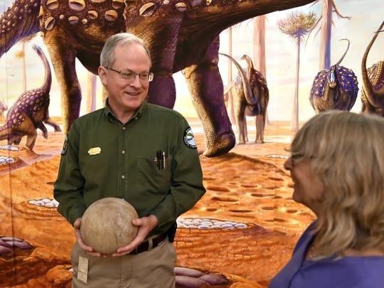 Paleontology curator George Phillips holds a Titanosaur