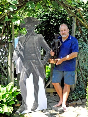 Wooster resident Jason Anderson holds an 18-inch bronze maquette of Gen. David Wooster beside a full-size poster replica of the statue to be erected in the lawn of the main branch of the Wayne County Public Library in Wooster.
