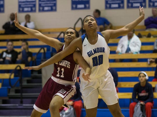 West Campus' Alexandra Dent (11) and Gilmour Academy's Naz Hillmon (00) get tangled while fighting for a rebound during the first half of action at Community School of Naples Friday, Dec. 30, 2016.