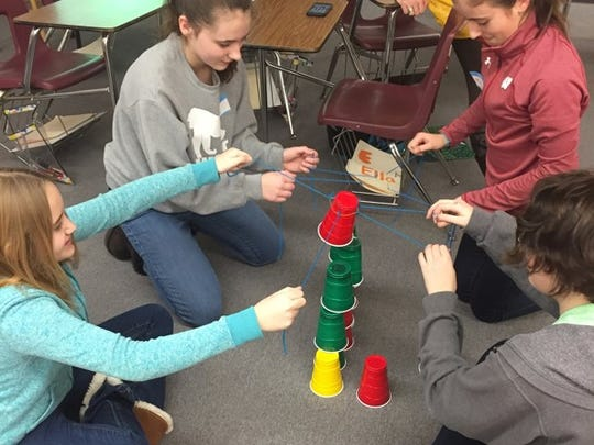 Girls in the Plymouth High School STEM Girls Rock club work through group problem solving with cups and string.