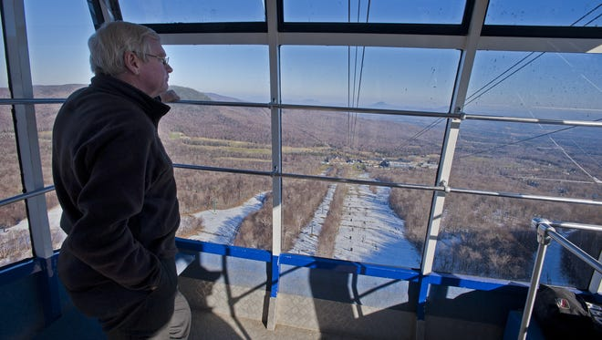 Jay Peak Resort president Bill Stenger looks out over the Northeast Kingdom as he rides down from Jay Peak on the resort's aerial tram on Monday, November 19, 2012.