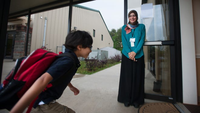 Yara Ibrahim, a teacher at As-Sabeel Academy, greets a student at the door for the start of school on Tuesday, May 3, 2016.