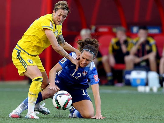 Jun 12, 2015; Winnipeg, Manitoba, CAN; United States midfielder Lauren Holiday (12) and Sweden midfielder Terese Sjogran (15) battle for the ball during the first half in a Group D soccer match in the 2015 FIFA women's World Cup at Winnipeg Stadium. Mandatory Credit: Bruce Fedyck-USA TODAY Sports
