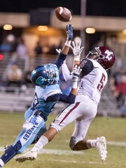 Redwood's Zedrik Ramos blocks a pass to Mt. Whitney's Mike Mckernan in the annual Cowhide football game on Friday, October 26, 2018.