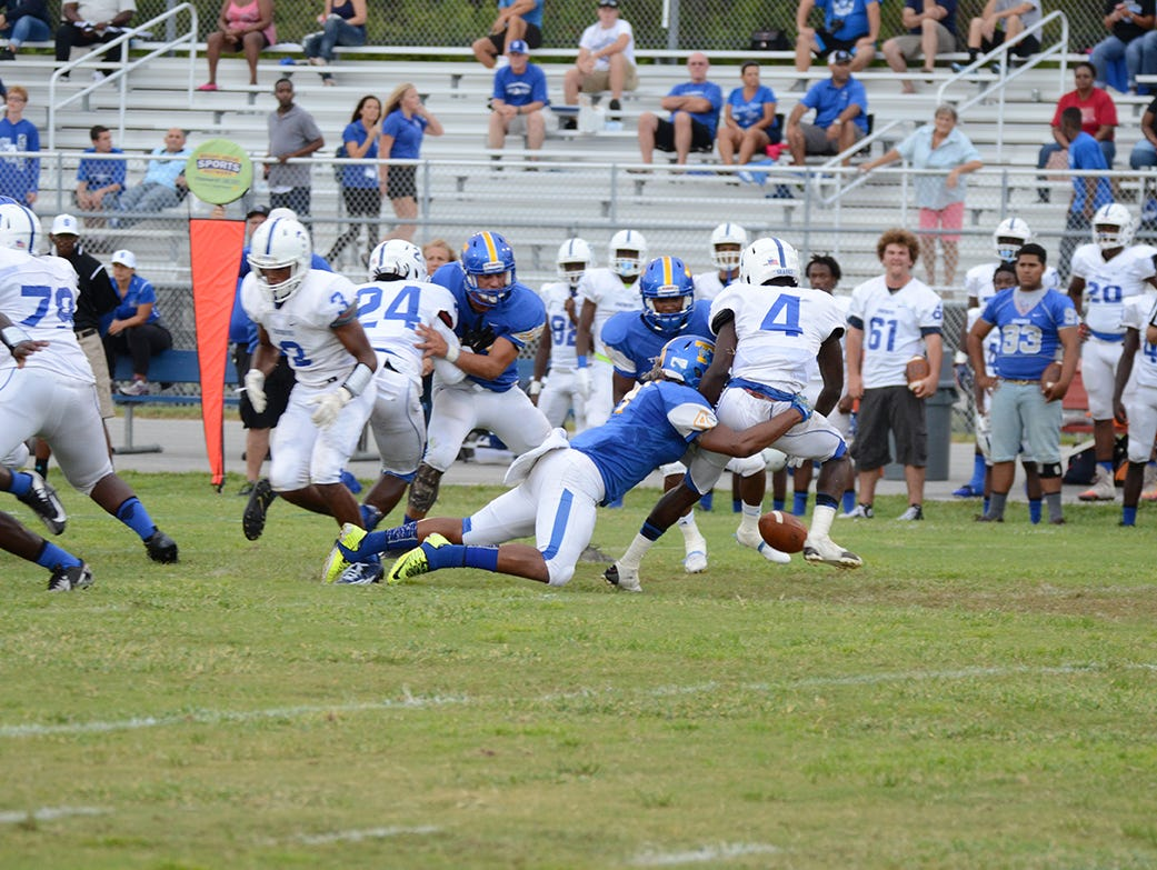 Bobby Bruce of Titusville causes Danuel Oscar of Sebastian River to fumble the ball two weeks ago at Titusville. (photo by Tony Dees/Florida Today)