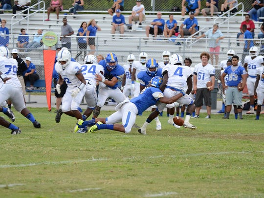 Bobby Bruce of Titusville causes Danuel Oscar of Sebastian River to fumble the ball in a game at Titusville.