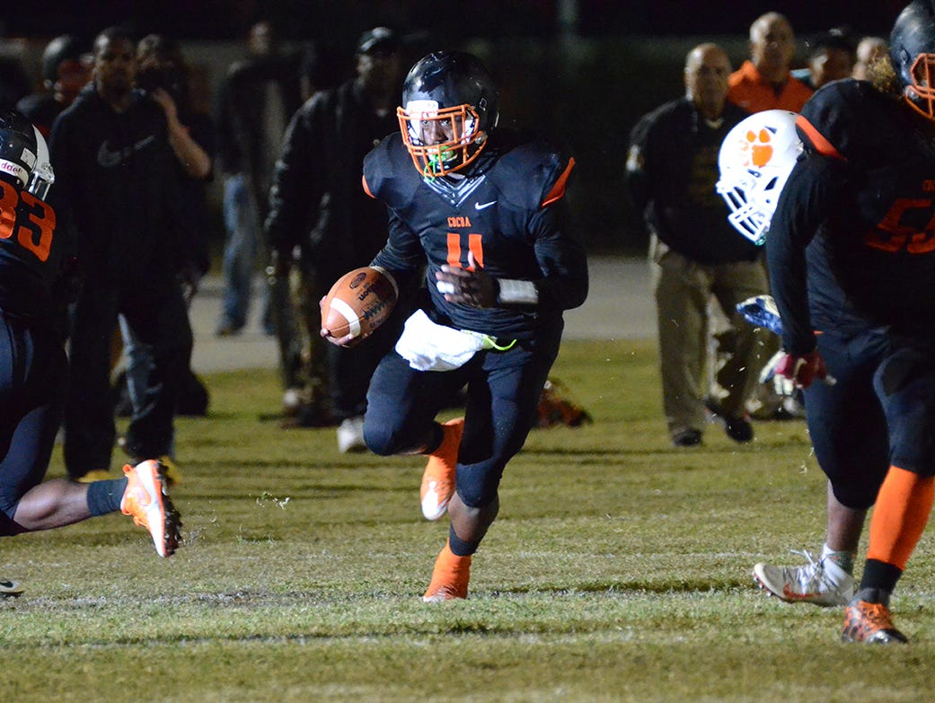 With his eye down field, Bruce Judson carries the ball Friday night in their showdown at home against Jones High School.