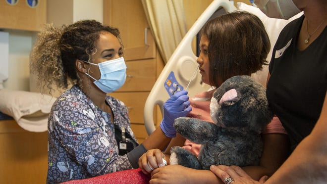 R.N. Kiyah Williams uses a swab to take a sample from Marieange Modeste as her mother, Kim Ruscher, sits next to her during filming of the test by PeaceHealth for distribution to the public to heighten awareness among families about what is involved in taking the test. [Andy Nelson/The Register-Guard] - registerguard.com