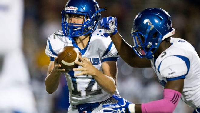Barron Collier quarterback Jacob Kuhlman (12) hands the ball of to running back Dana Brown (3) in the first half of action at Naples High School Friday, October 28, 2016 in Naples. Naples led 28-7 over Barron Collier at the half.