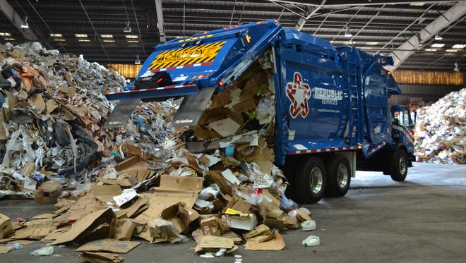 A truck unloads recycled material at a facility owned by Phoenix-based Republic Services.