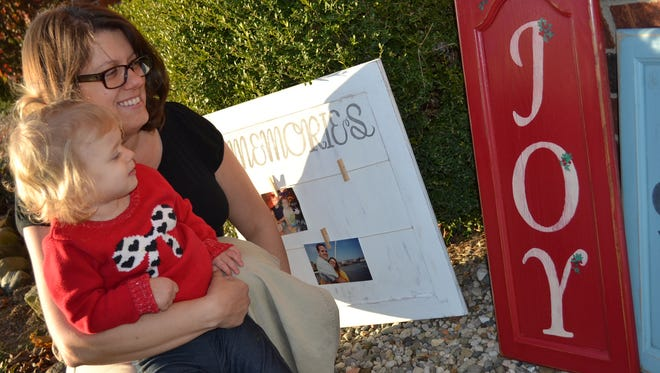 Bethany Ash and her daughter, Addy, with some of the pieces Bethany created by repurposing old kitchen cupboard doors. Ash encourages others to try the hobby she turned into a business, because, she said, mistakes can be simply sanded away.