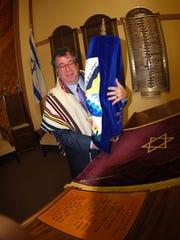 Sam Kimelman holds the Torah at Congregation Shomrei Torah.