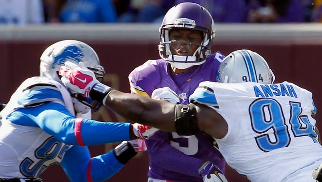 Minnesota Vikings quarterback Teddy Bridgewater is rushed by Detroit Lions defensive end George Johnson (93) left, and defensive end Ezekiel Ansah (94) after releasing the ball during the second half of an NFL football game Sunday, Oct. 12, 2014, in Minneapolis.