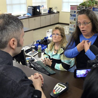 Rowan County Clerk Kim Davis, right, wound up in jail for contempt of court for her refusal to issue marriage licenses at the Rowan County Courthouse in Morehead, Ky.