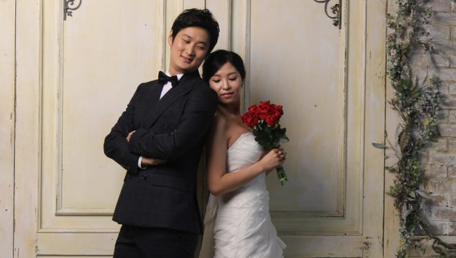 In this Tuesday, July 30, 2013 photo, Chen Jingjing, left, and Yang Candi of Beijing, China, strike a pose at a wedding studio in southern Seoul, South Korea, during an eight-hour photo session part of a South Korean wedding tourism package for Chinese couples. China is the source of one quarter of all tourists to South Korea, and a handful of companies in South Korea's $15 billion wedding industry are wooing an image-conscious slice of the Chinese jet set happy to drop several thousand dollars on a wedding album with a South Korean touch.