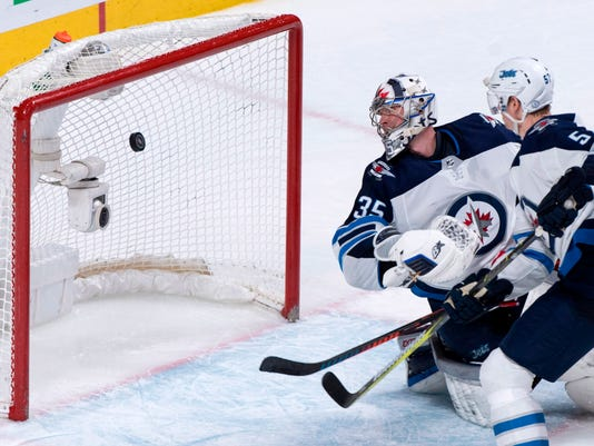 Winnipeg Jets goaltender Steve Mason and defenseman Tyler Myers watch the puck go into the net on a goal by Montreal Canadiens' Alex Galchenyuk during third period NHL hockey action Tuesday, April 3, 2018 in Montreal. (Paul Chiasson/The Canadian Press via AP)