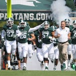 EAST LANSING, MI - SEPTEMBER 20: Michigan State Spartans head football coach Mark Dantonio leads his team onto the field prior to the start of the game against the Eastern Michigan Eagles at Spartan Stadium on September 20, 2014 in East Lansing, Michigan. Michigan State defeated Eastern Michigan 73-14 (Photo by Leon Halip/Getty Images)