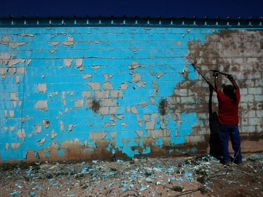 Phil Dee works on Monday to remove paint from a wall of the arts and crafts exhibit hall at the Northern Navajo Nation Fairgrounds in Shiprock.