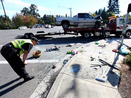 Salem police conduct a full traffic reconstruction after a crash on Kuebler Boulevard at Sunnyside Road SE involving a pickup truck and a SUV, Thursday, Oct. 1, 2015, in Salem, Ore.