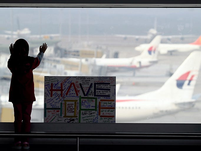 A girl stands with a sign dedicated to passengers aboard a missing Malaysia Airlines aircraft on March 10 at Kuala Lumpur International Airport in Sepang, Malaysia.