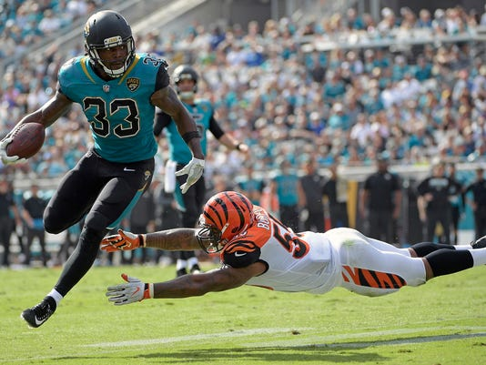 Jacksonville Jaguars running back Chris Ivory (33) gets around Cincinnati Bengals linebacker Vontaze Burfict, right, during the first half of an NFL football game, Sunday, Nov. 5, 2017, in Jacksonville, Fla. (AP Photo/Phelan M. Ebenhack)