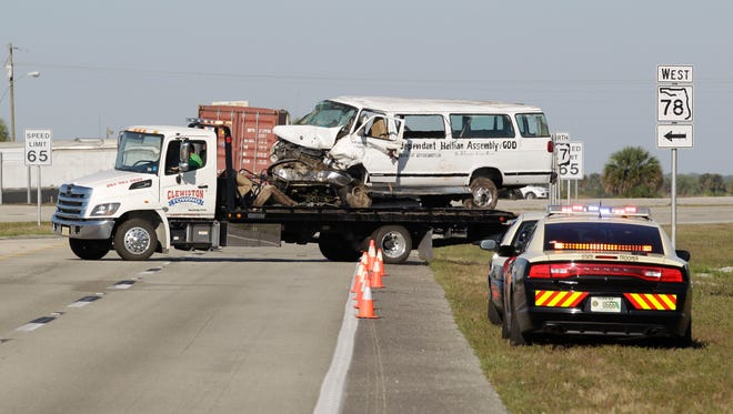 A tow truck moves a  van that crashed into a canal  Monday, March 30, 2015, near Moore Haven, Fla.