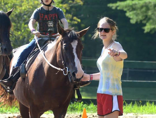 The Girl Scouts of America organization has expressed concern about the Boy Scouts plans to allow girls into that program. Girl Scouts contends it offers a wide variety of programs and activities geared specifically for girls. In this 2013 file photo, camp counselor Charlotte Hunter gives instructions to Kelly Derby as she learns about horseback riding.
