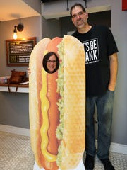 Jeanne Muchnick tries on the cardboard cutout next to owner Dennis Rubich, at The Dog Den, a new hot dog establishment at 1 Main Street in White Plains, July 6, 2018.