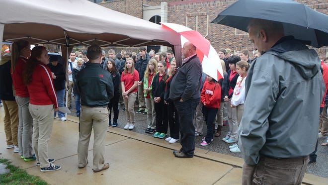 St. Philip Catholic Central High School students, faculty, and parents gathered at the grotto Tuesday afternoon to remember and pray for Tim May, the school's principal, who died suddenly on Monday.